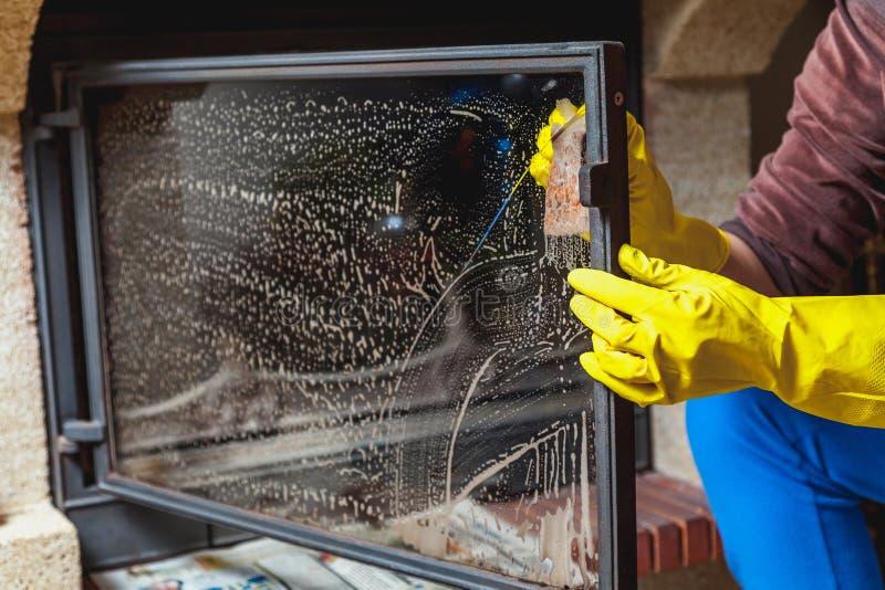 Händer i gula handskar tvättar den glass spisdörren arkivfoto