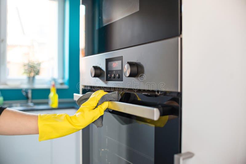 Händer i gula skyddande rubber handskar som gör ren ugnen royaltyfria bilder