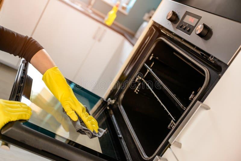 Händer i gula skyddande rubber handskar som gör ren ugnen arkivfoto