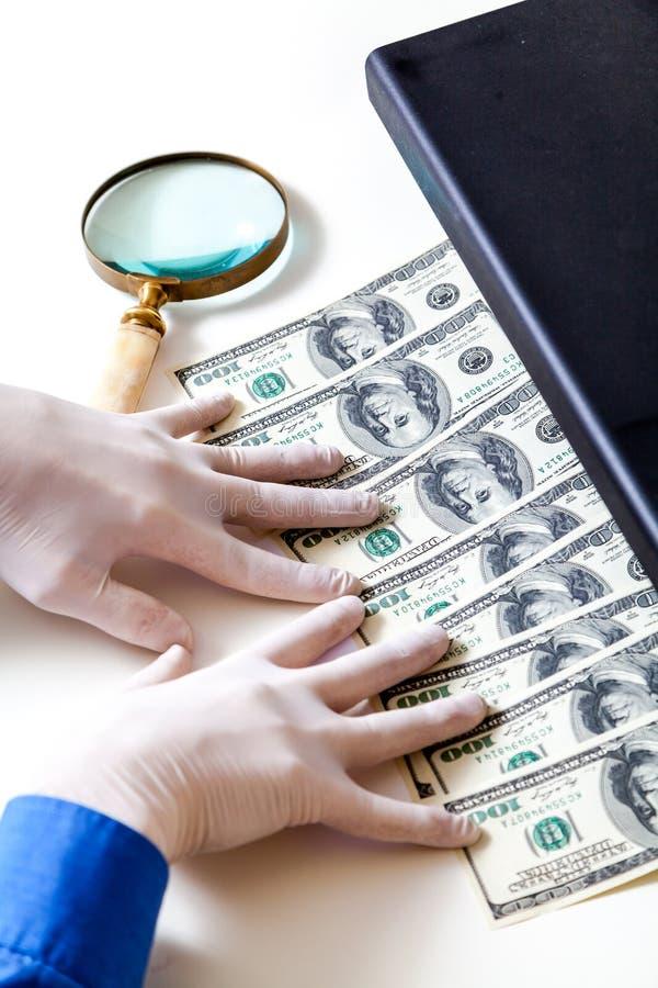 Händer i handskar kontrollerar dollarräkningar på avkännare fotografering för bildbyråer