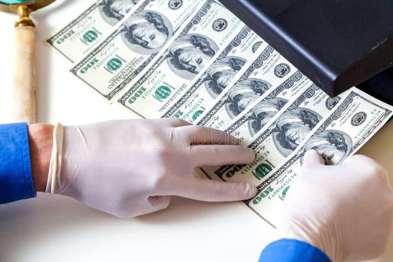 Händer i handskar kontrollerar dollarräkningar på avkännare arkivbild