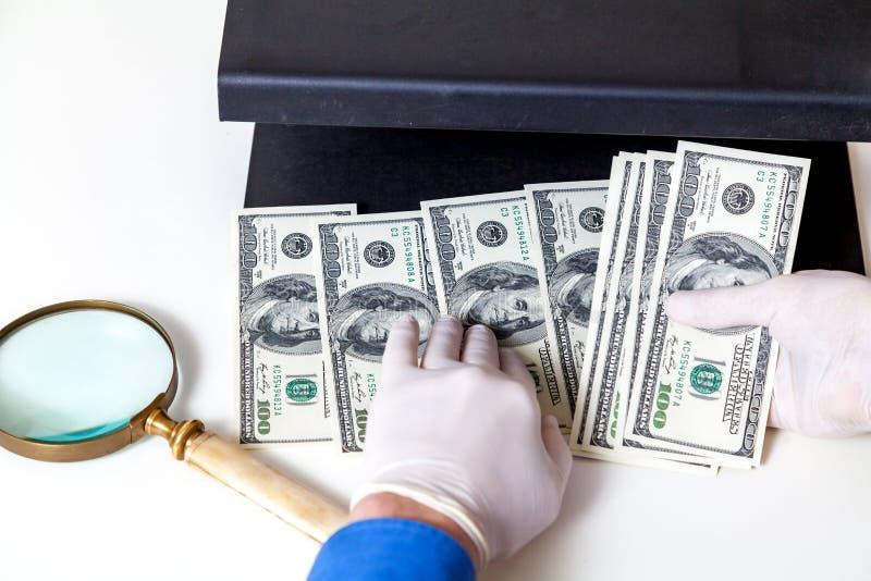 Händer i handskar kontrollerar dollarräkningar på avkännare royaltyfria foton