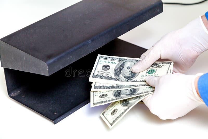 Händer i handskar rymmer fanen av den främsta avkännaren för dollar arkivfoto