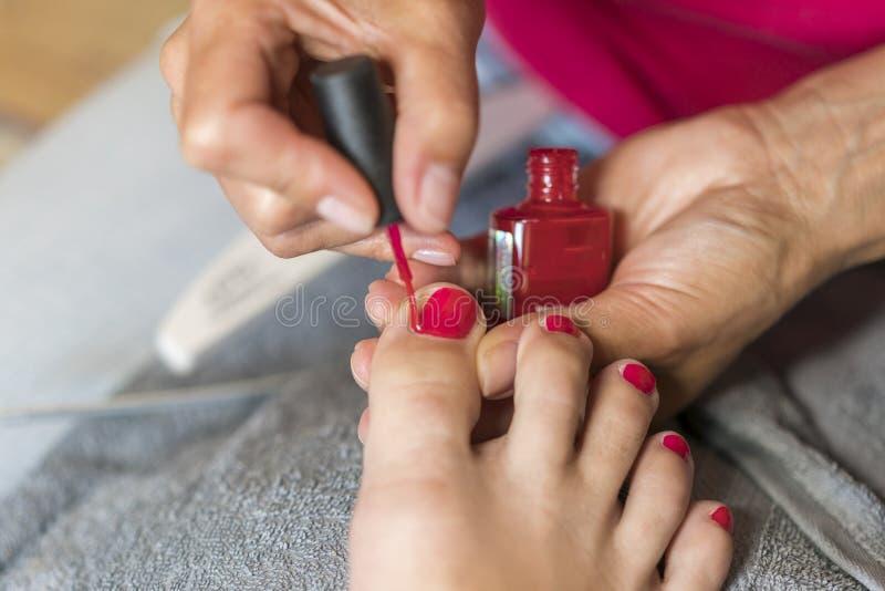 Händer i handskeomsorger om en kvinnas fot spikar Pedikyr begrepp för manikyrskönhetsalong Spika att lacka i röd färg arkivbilder
