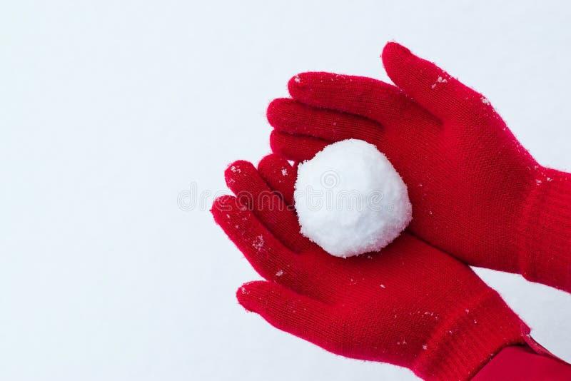 Händer i rött rymma för handskar kastar snöboll royaltyfri bild