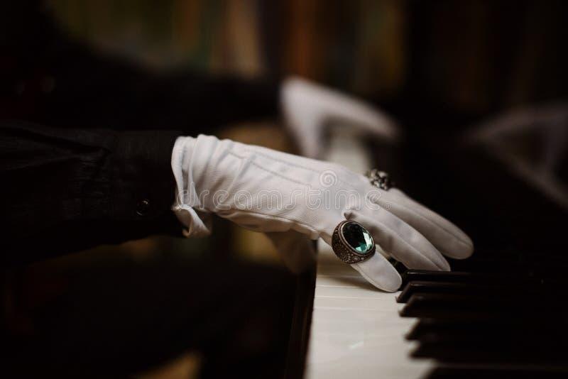 Händer i vita handskar med cirklar spelar pianot royaltyfri fotografi