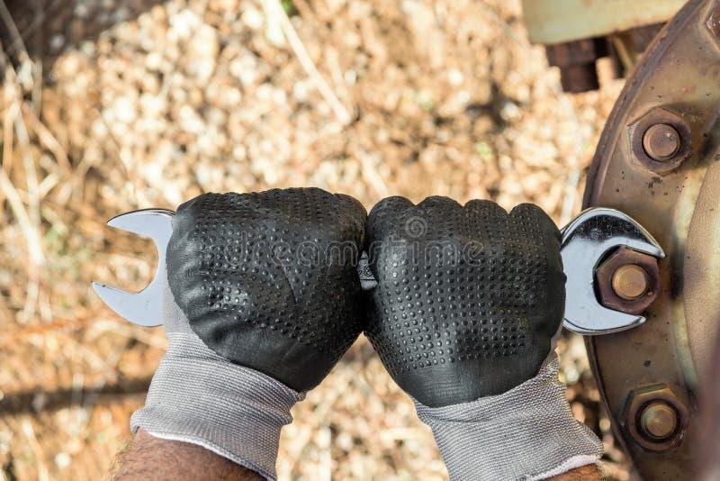 Händer med arbetshandskar som rymmer en skiftnyckel och, drar åt mycket Rusty Bolts royaltyfria bilder
