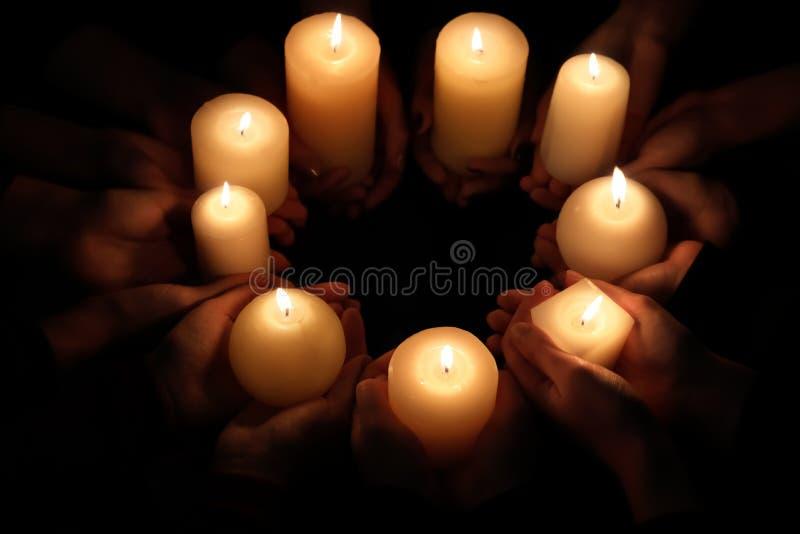 Händer med bränningstearinljus arkivfoto
