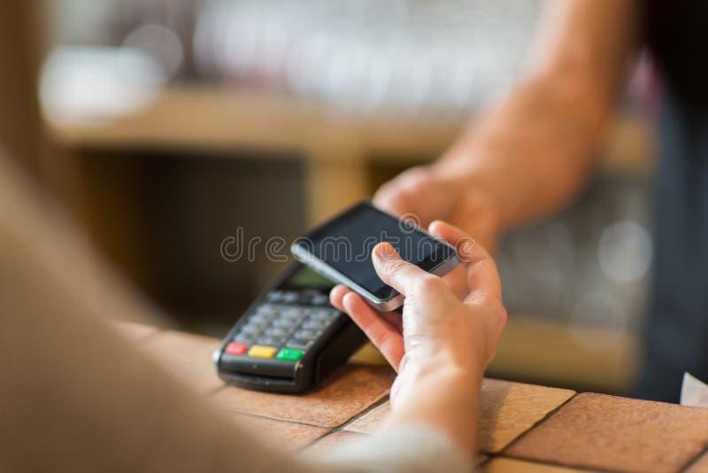 Händer med den betalningterminalen och smartphonen på stången royaltyfri foto