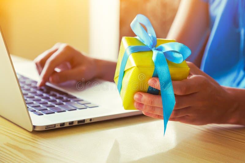 Händer med den gåvaasken och bärbara datorn royaltyfri foto
