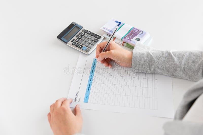 Händer med den skattformen, räknemaskinen och pengar på tabellen arkivbild