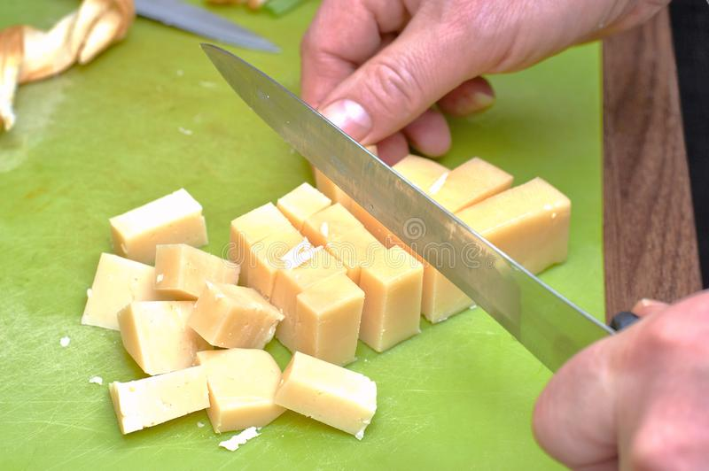 Händer med en kniv klippte osten in i kuber, närbild royaltyfria bilder