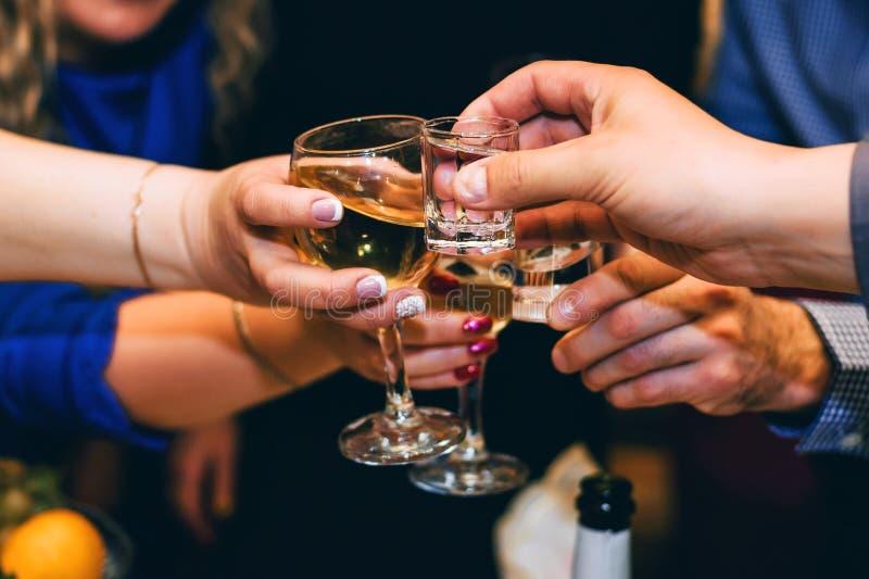 Händer med exponeringsglas av vin- och vodkavänner firar royaltyfri foto