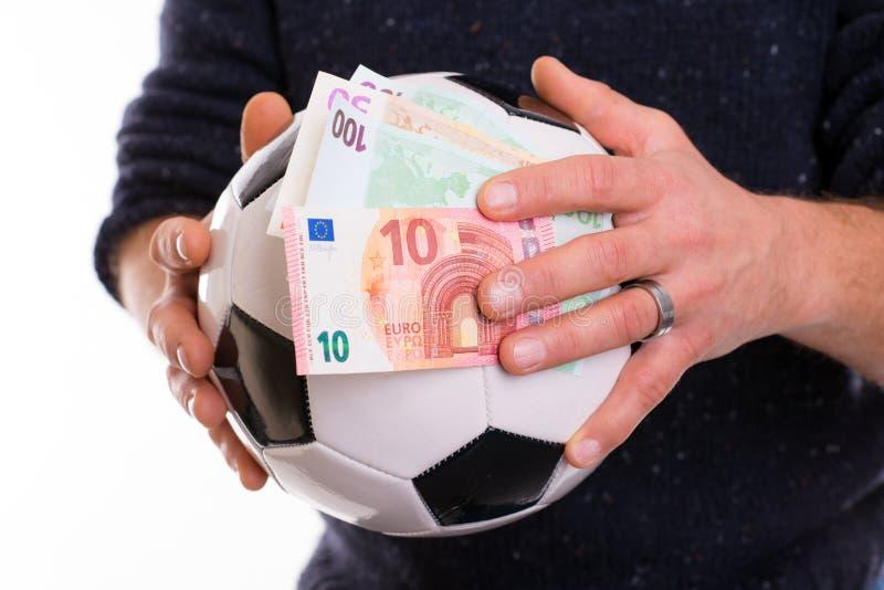 Händer med fotboll - boll och pengar royaltyfria bilder