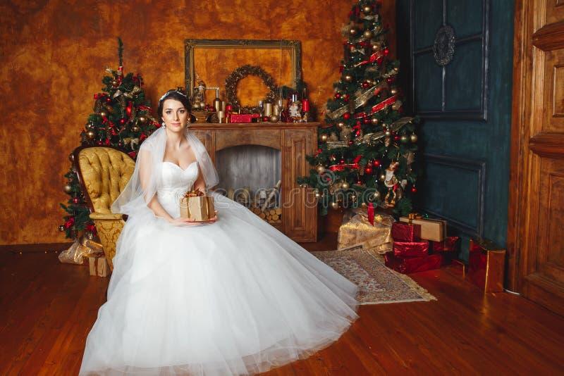 Händer med gåvaasken på bröllopberömmen Studiostående av den härliga bruden med gåvan Hållande gåva för brud Jul royaltyfri foto