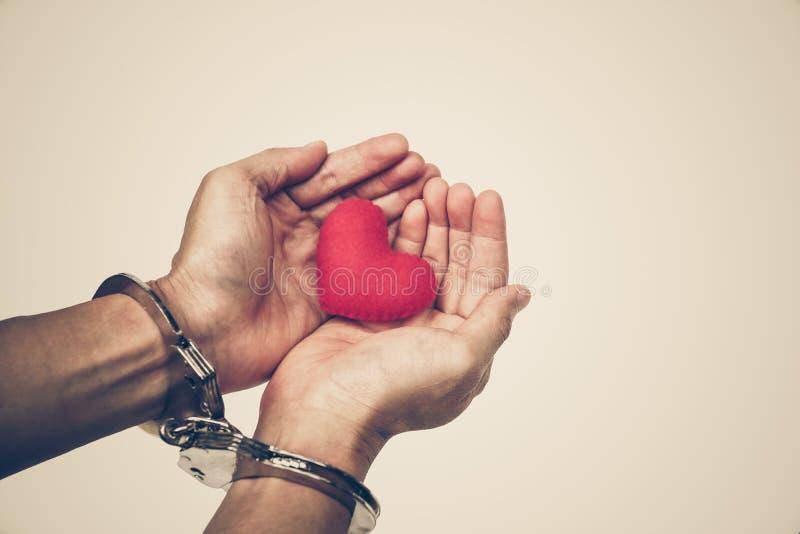 Händer med handbojor som rymmer en röd hjärta royaltyfria foton