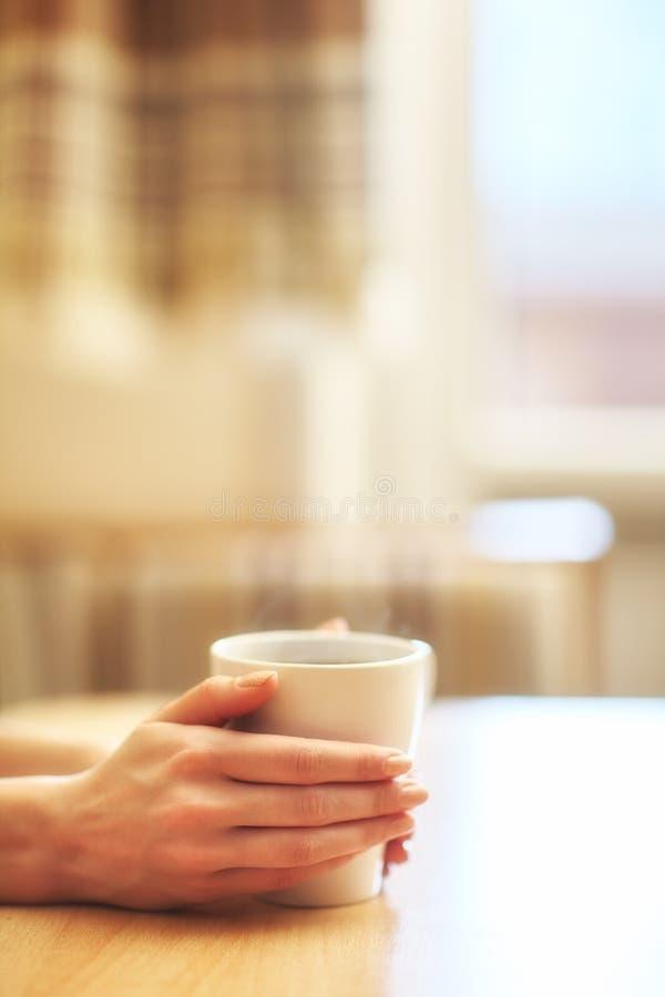 Händer med koppen av varmt morgonkaffe royaltyfri bild