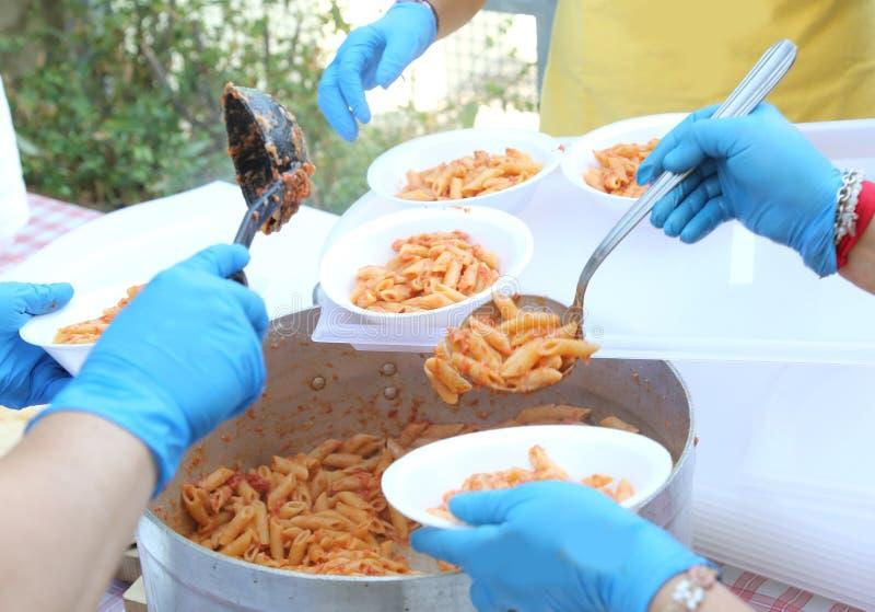 händer med latexhandskar under målfördelning av pasta med t royaltyfri bild