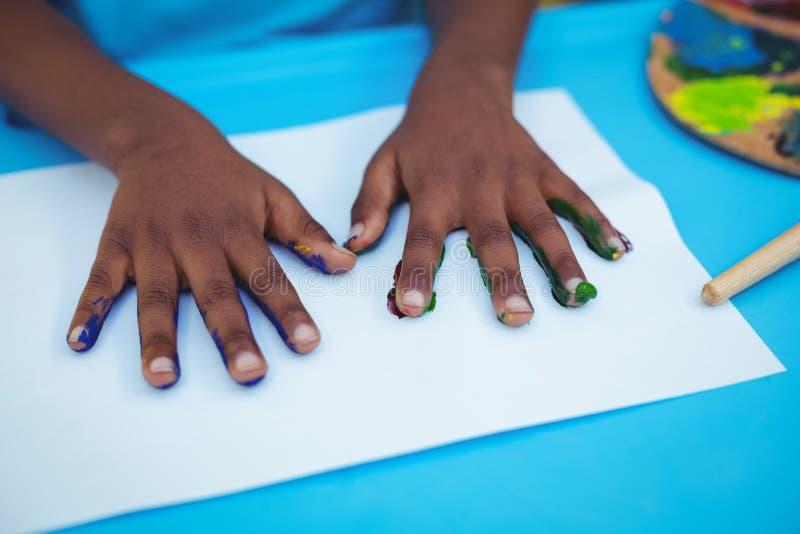 Händer med målarfärg på dem på papper fotografering för bildbyråer