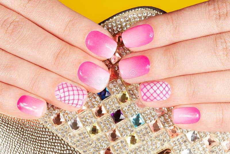 Händer med manicured spikar dolt med rosa färger spikar polermedel på kristallbakgrund royaltyfri fotografi