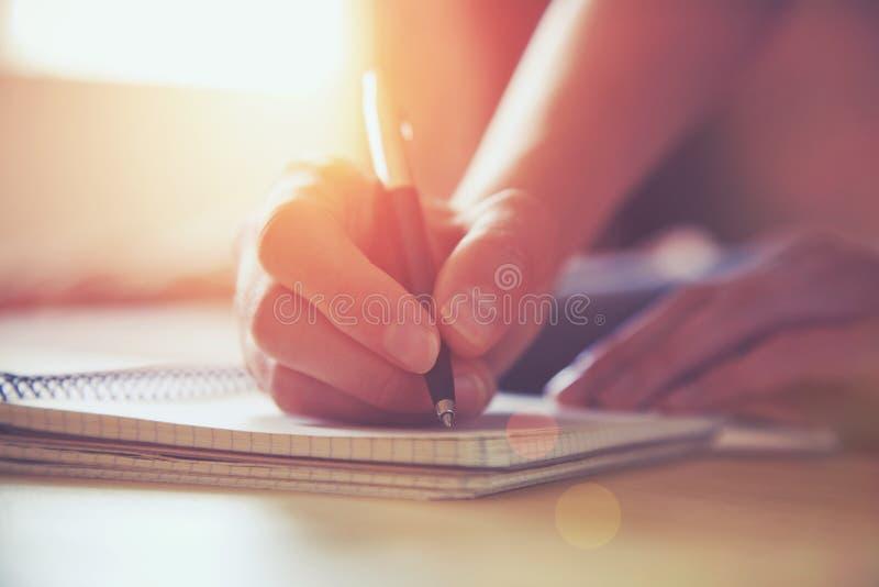 Händer med pennhandstil på anteckningsboken royaltyfri foto
