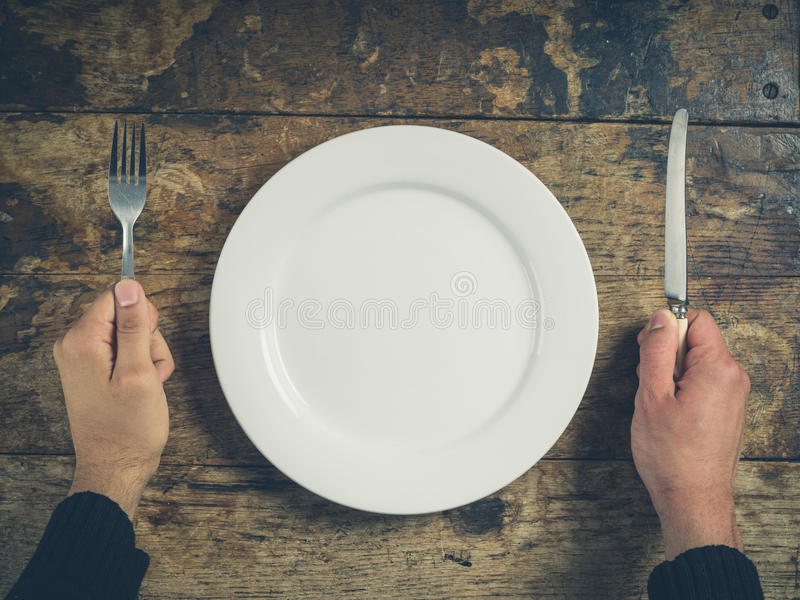 Händer med plattan, kniven och gaffeln arkivfoton