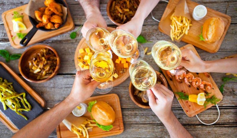 Händer med rött vin som rostar över den tjänade som tabellen med mat royaltyfria foton