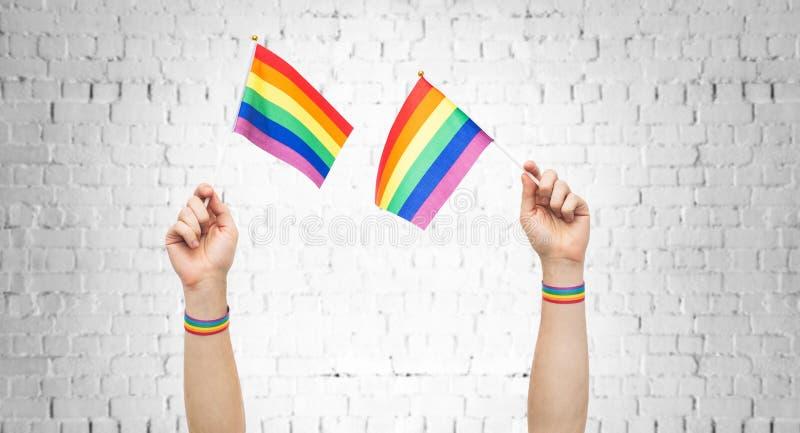 Händer med regnbågeflaggor och armband för glad stolthet arkivbilder