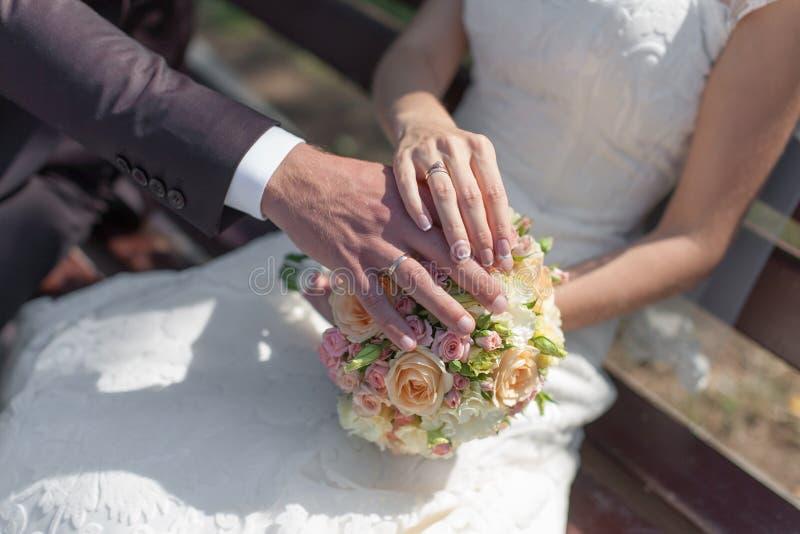 Händer med vigselringar på brud- bukett royaltyfri foto