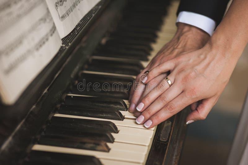 Händer med vigselringar på piano royaltyfria bilder