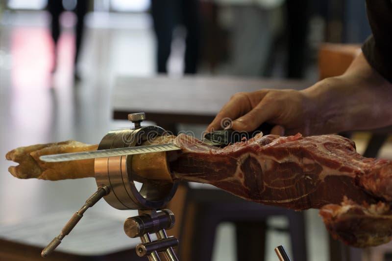Händer, medan klippa spansk skinka royaltyfria foton