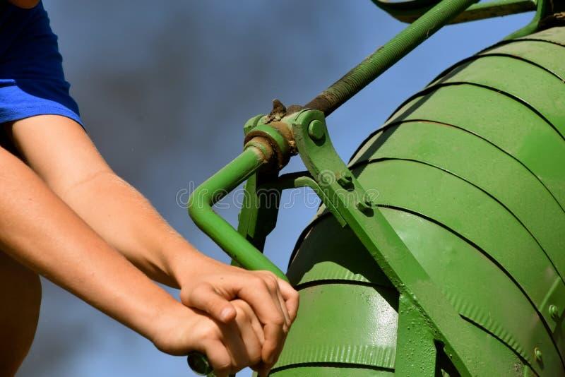 Händer och armar vänder blåsaren vever tröska - maskinen royaltyfri foto