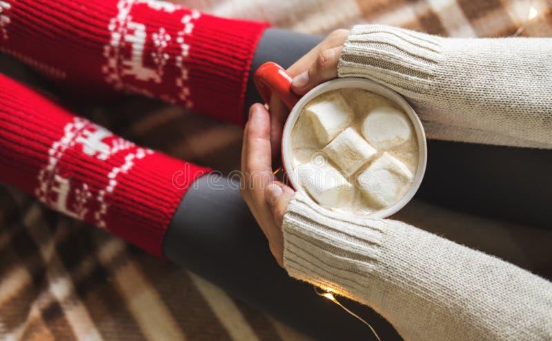 Händer och fot för kvinna` s i tröjan och woolen hemtrevliga röda sockor som rymmer koppen av varmt kaffe med marshmallowen som s arkivfoto