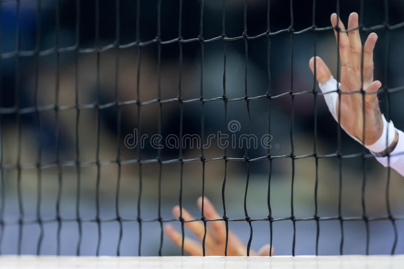 Händer på netto under den hellenska volleybollligaleken arkivbild