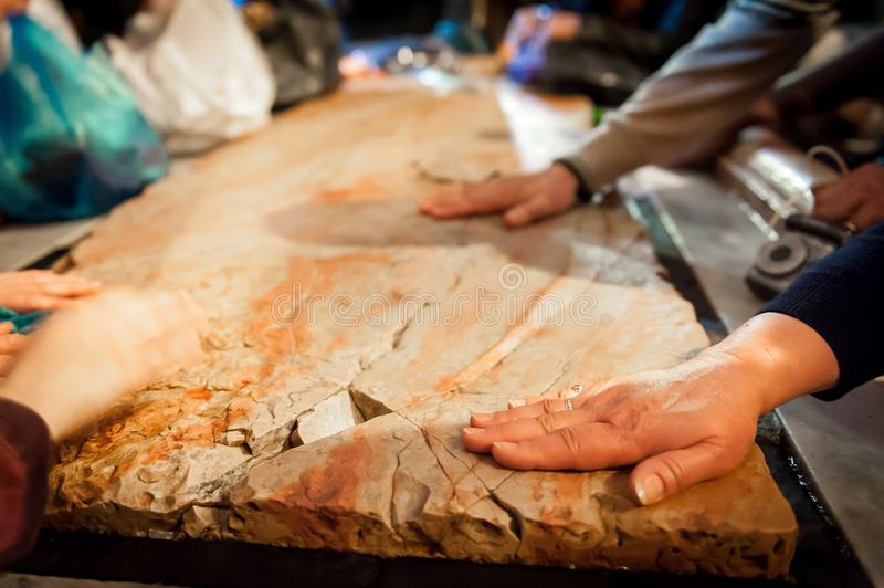 Händer på stenen av smörja royaltyfri bild