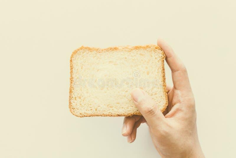 Händer rymmer en skiva av bröd på vit bakgrund royaltyfri bild