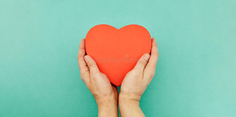 Händer rymmer röd hjärta som äldre omsorgbegrepp arkivfoton