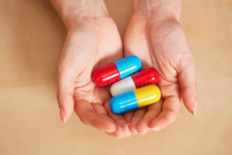 Händer rymmer tre stora piller eller mediciner royaltyfri fotografi