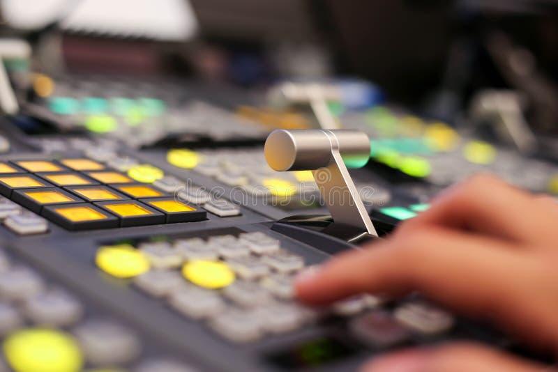 Händer skjuter en knapp av Switcherknappar i studioTV-station, Au arkivbilder