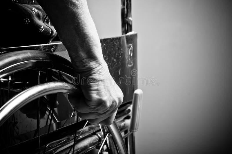 Händer som är höga i rullstol fotografering för bildbyråer