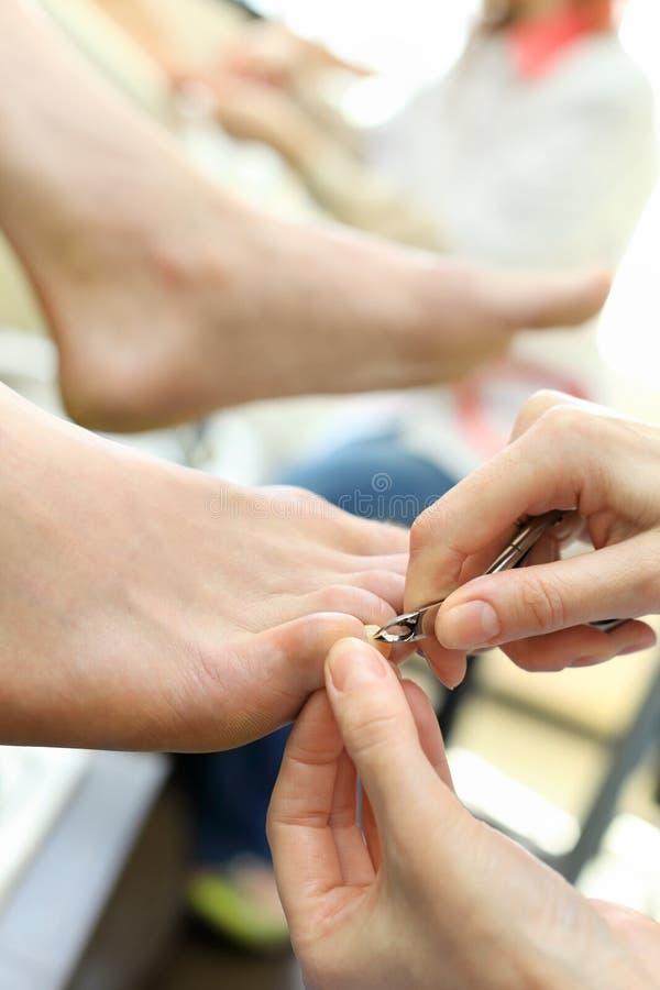 Händer som öva chiropody som tar omsorg av fot fotografering för bildbyråer