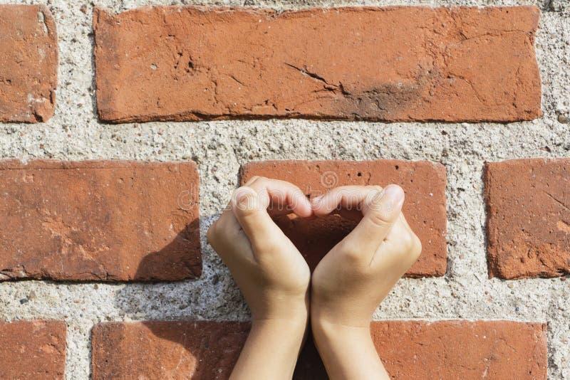 Händer som bildar en hjärta med händer som bildar en hjärtaskugga på en tegelstenvägg i solskenet royaltyfria bilder