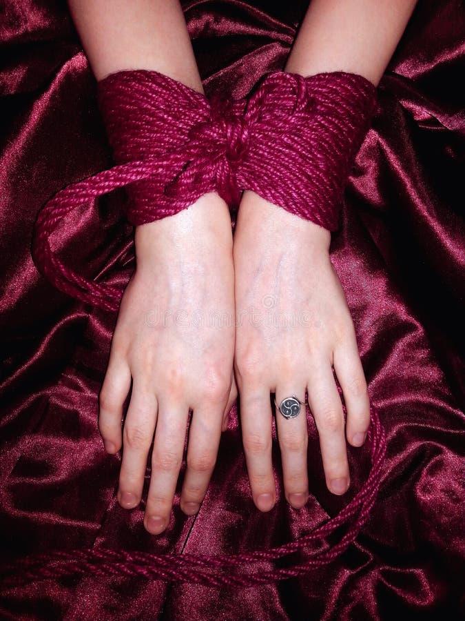 Händer som binds med det röda repet arkivbilder