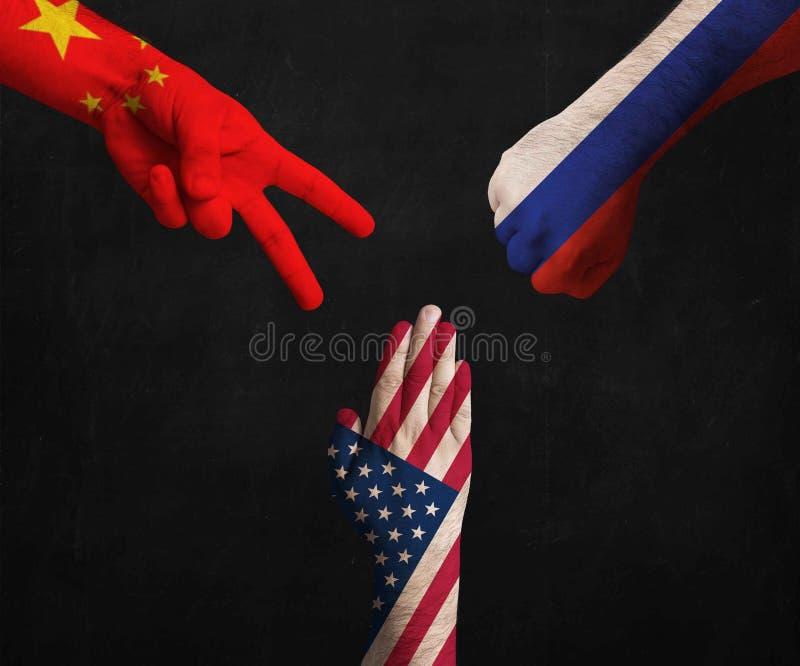 Händer som dekoreras i flaggor av Kina, för Amerikas förenta stater och för rysk federation visningsax, papper, sten arkivfoto