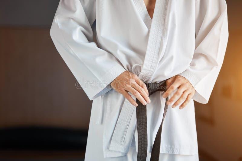 Händer som drar åt det svarta bältet på den iklädda kimonot för man arkivfoton