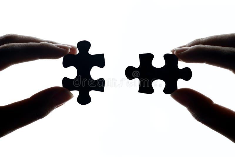 Händer som förbinder pusselstycken arkivfoto