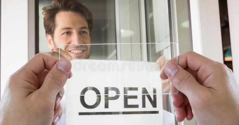 Händer som fotograferar det öppna tecknet till och med den genomskinliga apparaten medan man som ler i coffee shop arkivfoton