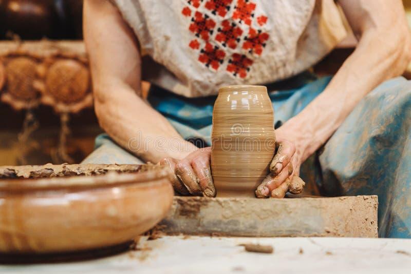 Händer som fungerar på krukmakerihjulet royaltyfria foton