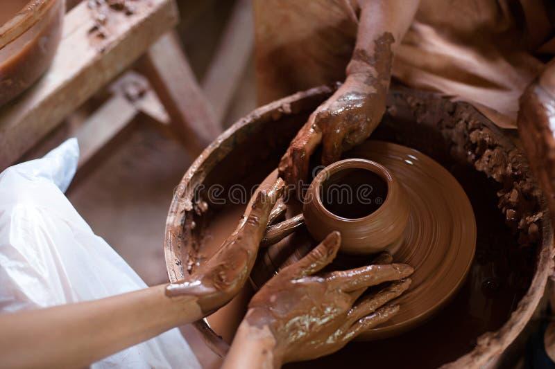 Händer som fungerar på krukmakerihjulet Slut upp av Ceramisthänder på arbete i hennes seminarium arkivfoto