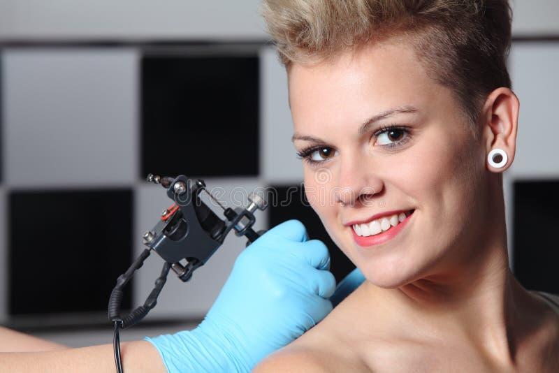 Händer som gör en tatuering på en kvinnaskuldra royaltyfria bilder